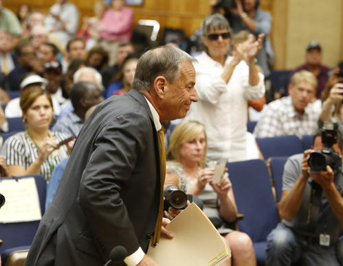Bob Filner enters the San Diego council chambers to announce that he is resigning as mayor as his supporters applaud in the background. He was publicly accused of sexual harassment by many women.