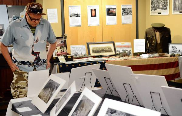 Graham Elliott of Jersey City, N.J., looks at Holocaust photos at the Legacy Exhibit at the Sigal Museum in Easton on Sunday.