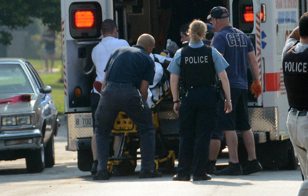 Chicago police load a victim into an ambulance after a shooting incident in the 8300 block of South Baltimore Avenue in Chicago.