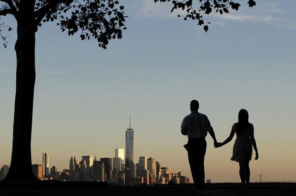 The rebuilt skyline of New York's lower Manhattan is the view for a couple walking Sunday in a Weehawken, New Jersey park.