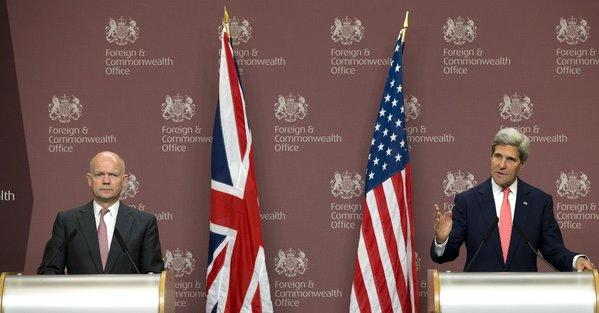 Britain Foreign Secretary William Hague, left, looks on as Secretary of State John F. Kerry speaks at a news conference in London on Monday.