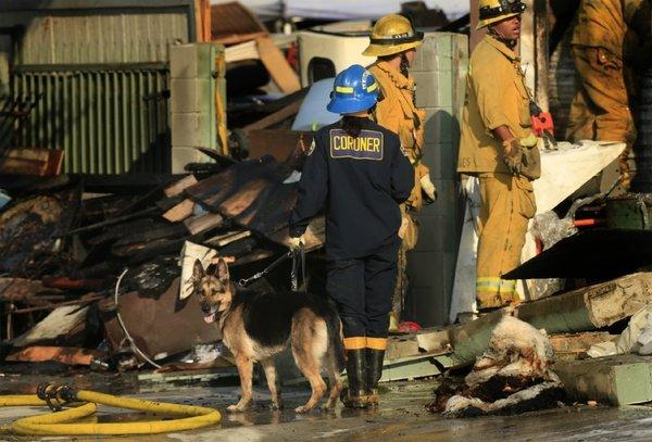 L.A. County coroner K-9 handler Karina Peck guides her human remains detection canine through the rubble left by a fire at 4319 E. Compton Blvd. on Monday.