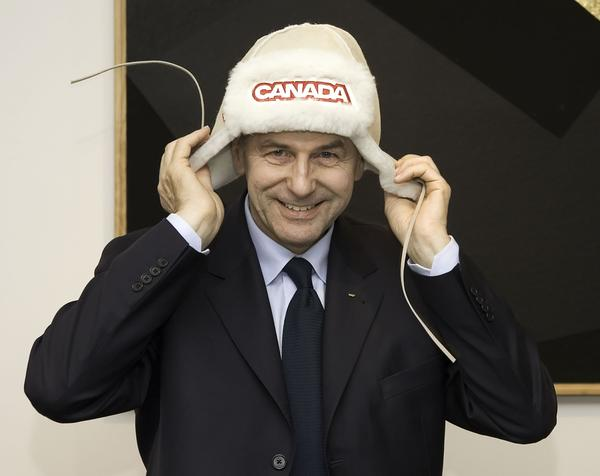 In a rare lighthearted moment, IOC President Jacques Rogge tries on a Canada Olympic team hat during the 2006 Turin Winter Games.