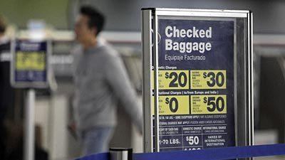 A traveler walks past a sign displaying fees for checked baggage on American Airlines.