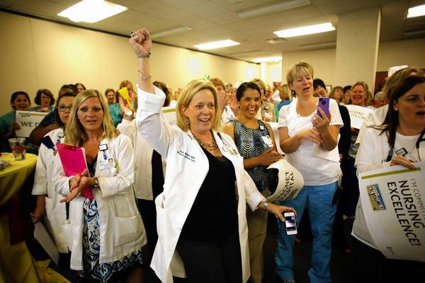 Susan Whildrin, director of clinical care services, center, begins the whooping to celebrate, July 16, 2013 in Geneva. More than 150 Delnor Hospital nurses, clinical and support staff, cheer the official phone call on a conference call from the American Nurses Credentialing Center announcing that they will receive re-designation of Magnet status.