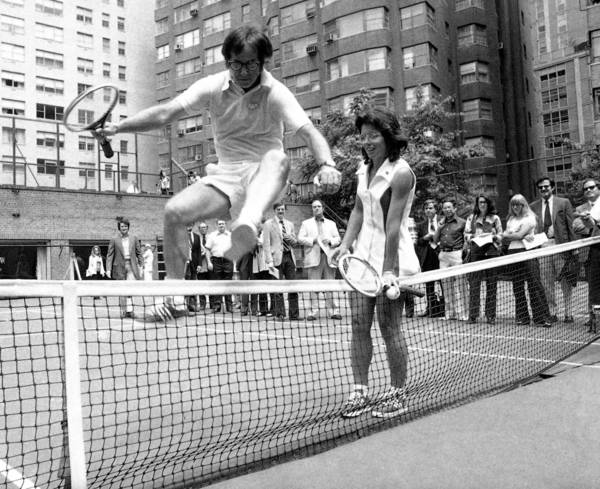 "Billie Jean King holds down the net as Bobby Riggs, the 55-year-old tennis player she played in the game that was billed as ""the battle of the sexes,"" jumps over."