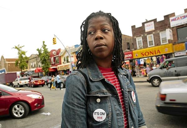 Naquasia LeGrand, 22, works at two KFC restaurants in New York, including the one in Queens behind her. She's helping to organize protests by fast-food workers.