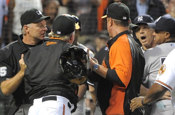 Oriole' manager Buck Showalter is held back by homeplate umpire Ed Hickox as Showalter and Yankees manager Joe Girardi have words in the first inning. Baltimore Orioles vs. New York Yankees at Camden Yards.