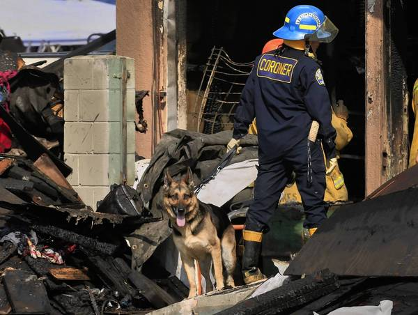 L.A. County Coroner K-9 handler Karina Peck guides her human remains detection canine through the rubble left by a fire near Compton on Monday. The bodies of a woman and a girl were found in the back of the mechanic shop, officials said. The upstairs had been converted into an illegal loft and living space.