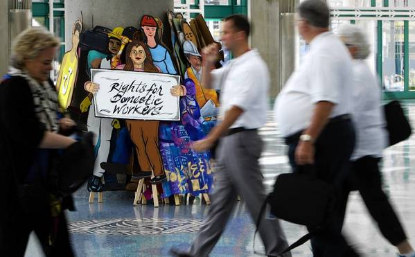 Attendees walk past cardboard cutouts of domestic workers during the annual AFL-CIO convention at the L.A. Convention Center on Monday.