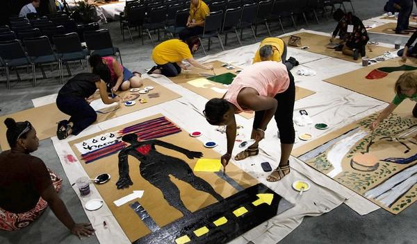 Shawdrica Simmons, left, and Shatoria Simmons of Detroit work on a cardboard cutout of a distressed black woman during the annual AFL-CIO convention at the Convention Center.