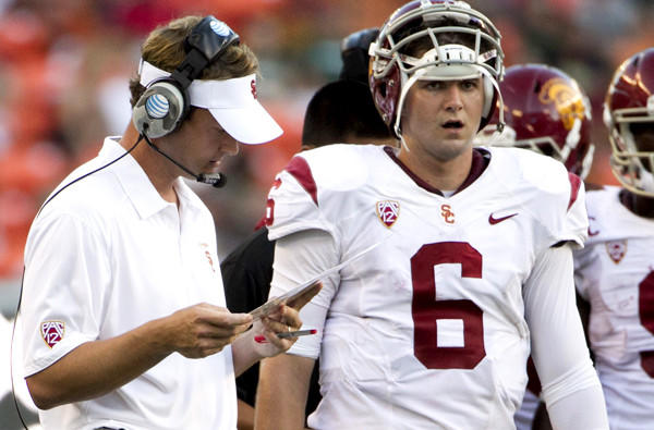 USC Coach Lane Kiffin looks over his list of plays next to quarterback Cody Kessler during the season-opening game in Hawaii.