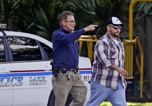 George Zimmerman, right, is escorted by a police officer in Lake Mary, Fla.