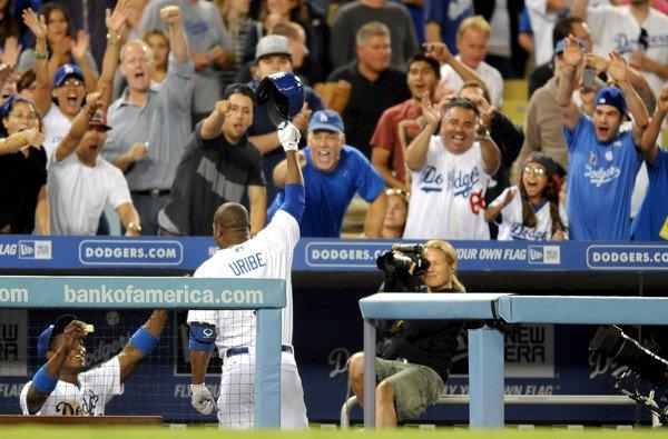 Dodgers third baseman Juan Uribe comes out of the dugout for a standing ovation in the fifth inning after hitting his third solo home run against the Diamondbacks on Monday night at Dodger Stadium.