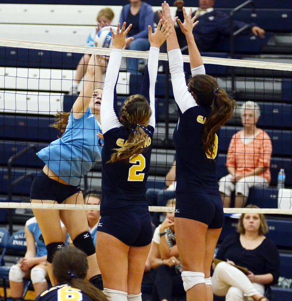 Petoskey senior Natalie Weaver (left) spikes the ball against the block of Gaylord junior Lindsey Zaremba (2) and senior Dakota Pelach (right) during Monday's Big North Conference match at the Petoskey High School gym.