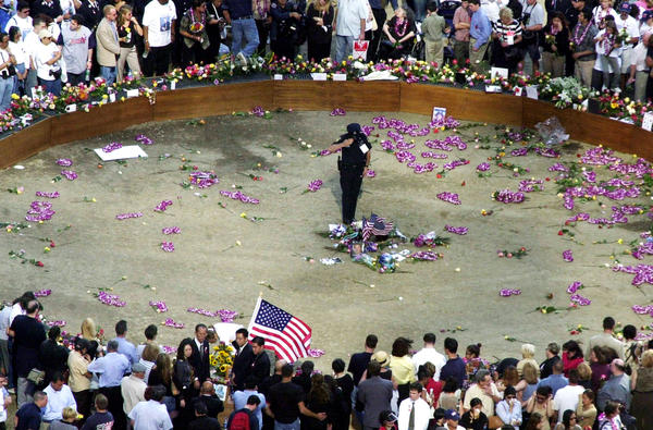 9/11 Anniversary - A lone policeman salutes in the circle of honor at ground zero during 9/11 ceremonies Wednesday. Family members that lost loved ones in the attack on the World Trade Center towers placed flowers ,flags and pictures at ground zero that will be part of ta memorial. (red huber/orlando sentinel)9-11 MEMORIAL