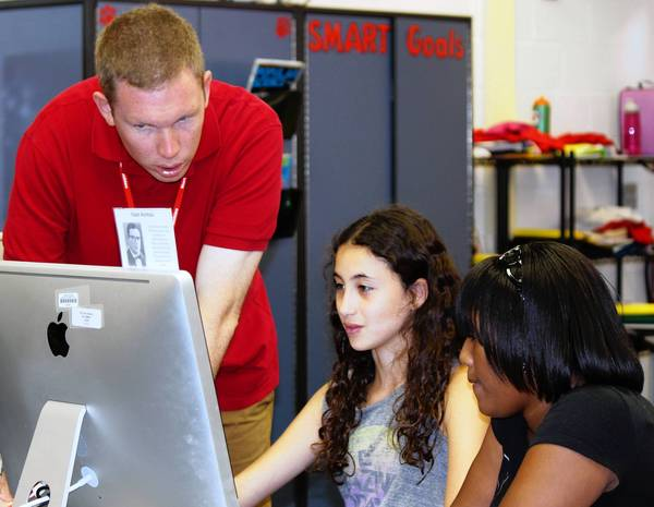 Northwood Junior High School STEM teacher Bill Steinbach confers with seventh graders Sara Stahlberger, center, and Trinity Hayes.