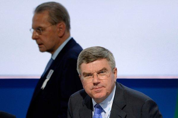 Changing of the guard: Outgoing IOC President Jacques Rogge walks behind new President Thomas Bach before Tuesday's election.