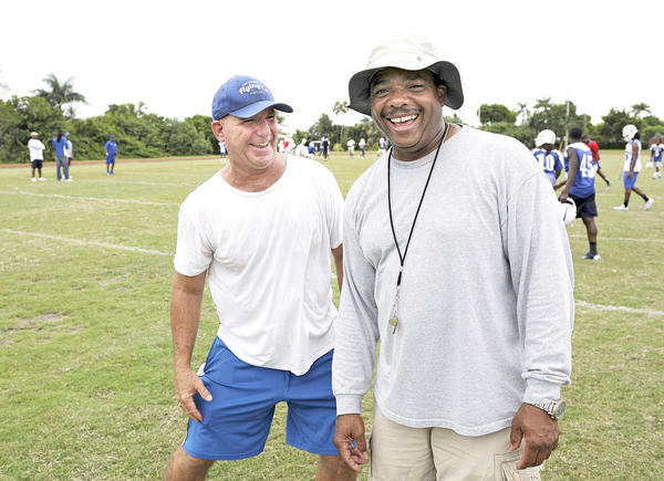 Patrick McGee, left, a Fort Lauderdale Fire Department driver/engineer, and Harvey Jacques, a sergeant with Fort Lauderdale Police Department spend their free time coaching football at Fort Lauderdale High School. Photo by Michael Laughlin.