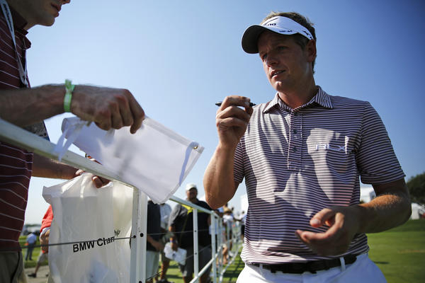 Luke Donald signs autographs after practicing on his chip shots at the 2013 BMW Championship at Conway Farms Golf Club in Lake Forest on Tuesday.