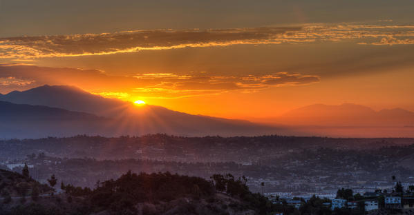 The sun can be seen rising over the mountains from Griffith Observatory.