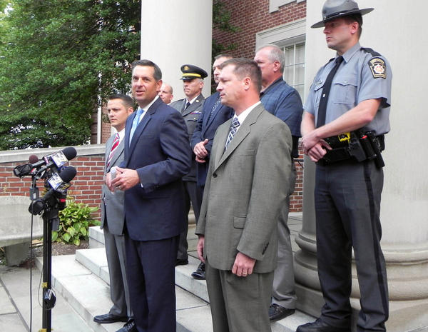 Cumberland County (Pa.) District Attorney David Freed, center, talks to the media Tuesday about a police chase that started as a bank robbery in Chambersburg, Pa., and ended with the death of the suspect in a field near Newville, Pa., in Cumberland County.