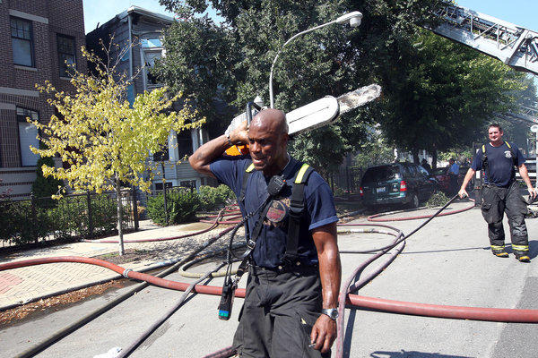 A firefighter carries a saw from the scene of a fire in Wrigleyville was worked by about 100 firefighters due to the heat.