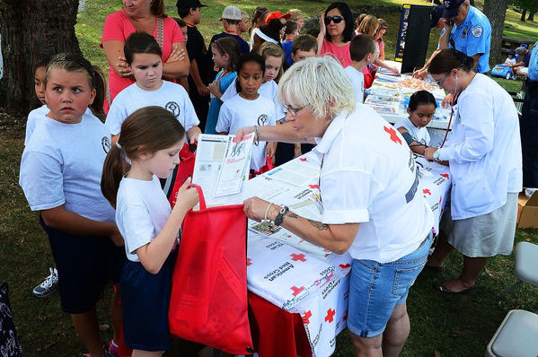 Michelle Beck, 8, is given information on emergency preparedness by Red Cross responder Leslie McIntosh at Preparedness in the Park in CIty Park in Hagerstown. Beck is a third-grader at St. Mary's Catholic School.