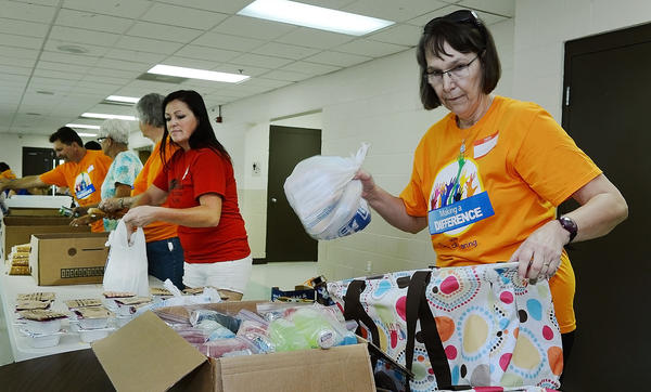 Joan Woody, along with others with the Berkeley County BackPack Program, places a bag of food items into a bag.