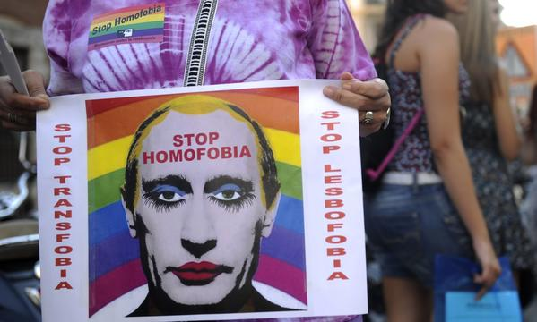 A Madrid demonstrator holds a poster depicting Russian President Vladimir Putin with make-up in protests against homophobia and repression against gays in Russia.