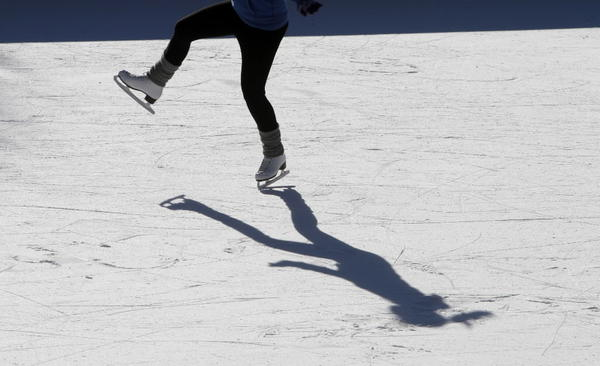 Emily Tarby, 15, and her shadow practice spins on the ice at the skating rink on the Midway Plaisance in Hyde Park. Mild temperatures and sun made this a snowless Christmas day.