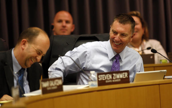 "LAUSD Superintendent John Deasy, right, and LAUSD board member Steven Zimmer enjoy a light moment during a school board meeting to vote on continued funding for a classroom breakfast program, an increase in the school police force and a new policy on ""willful defiance"" at the LAUSD Headquarters."