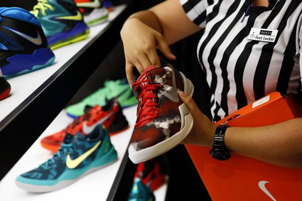 Nike Inc. will be part of the Dow Jones industrial average beginning Sept. 23. Above, an employee arranges Nike basketball shoes at Foot Locker at the Beverly Center in Los Angeles last month.