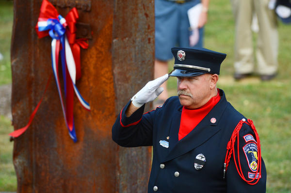 Hagerstown Fire Department Honor Guard member Ed Shindle salutes during the national anthem Tuesday at Remembrance in the Park.