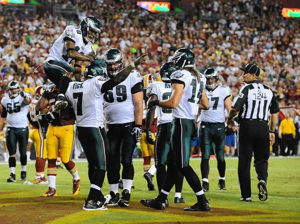 Sep 9, 2013; Landover, MD, USA; Philadelphia Eagles quarterback Michael Vick (7) is congratulated by a leaping Philadelphia Eagles wide receiver DeSean Jackson (10) after scoring a touchdown during the first half against the Washington Redskins at FedEX Field.