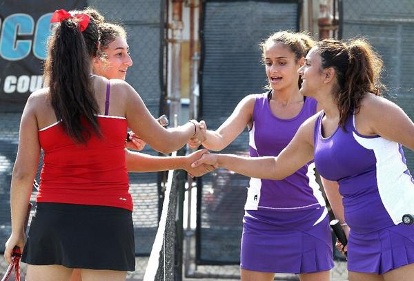 Glendale's Rouvana Hakobyan, from left, shakes hands with Hoover's Audria Amirian, and Glendale's Mary Pailevanian shakes hands with Hoover's Erlinda Kirakosyan at the conclusion of their doubles match. The Nitros posted a 13-5 victory over the Tornadoes.