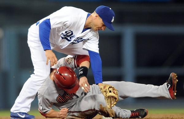 Dodgers second baseman Mark Ellis, top, collides with Arizona's Miguel Montero after turning a double play during the second inning of the Dodgers' 5-3 win Tuesday.