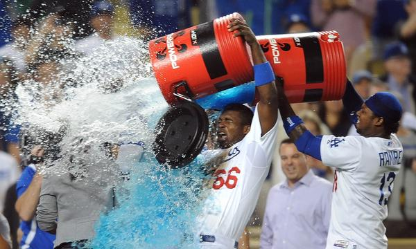Dodgers teammates Yasiel Puig, center, and Hanley Ramirez give Scott Van Slyke a watercooler shower after Van Slyke's pinch-hit, two-run home run in the 11th inning of the Dodgers' 5-3 win over the Arizona Diamondbacks on Tuesday.