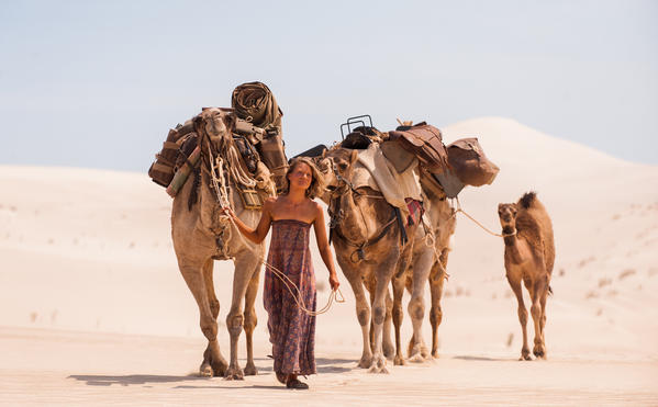 "Mia Wasikowska with her camel co-stars in ""Tracks."""