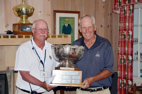 Bill Zylstra (right) of Grand Rapids receives the Golf Association of Michigan Senior Amateur Championship trophy from rules official Steve Braun after winning the two-day tournament at the Belvedere Golf Club in Charlevoix Tuesday.