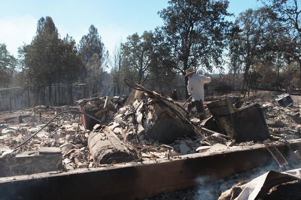Carl Reed helps his son-in-law, Sean Reed, go through the remnants of his home off Small Farms Drive on Tuesday after the Clover fire scorched the area.