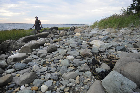 A woman walks along the rocky path that circles Charles Island.