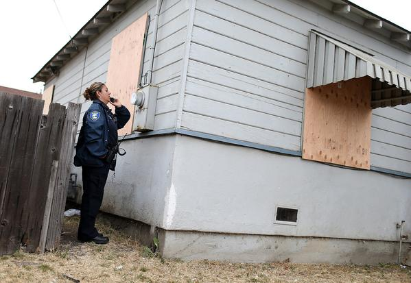 A code enforcement officer checks a meter at a foreclosed home in Richmond, Calif. The city is pressing ahead with a plan to buy or seize underwater home loans and write down the balances to lower payments for the homeowners.