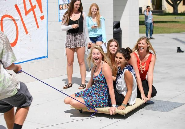 Physics teacher Lisa Taylor, far right, goes along for a ride with students Eliz Ghazarian, bottom right, Hailey Transue, bottom left, and Stephie Miller, sitting second from left, during a class activity at Huntington Beach High on Monday.