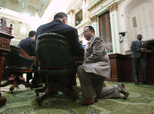 Assemblyman Luis Alejo (D-Watsonville), right, talks with Assemblyman Jose Medina (D-Riverside) during the Assembly session at the Capitol in Sacramento on Tuesday. On Wednesday, Alejo shelved a bill for the year that would provide driver's licenses to immigrants in the country illegally.