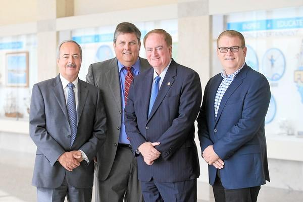 """Airport Director Alan Murphy, ExplorOcean CEO Tom Pollack, Newport Beach Mayor Keith Curry, and Newport Beach and Company President Gary Sherwin, from left to right, pose for a photo on Monday in front of the ExplorOcean exhibit titled """"Inspire, Educate, Explore: ExplorOcean,"""" on display through Nov. 15 at John Wayne Airport."""