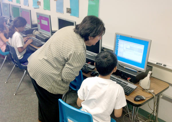 Vicki Brown instructs a student at a computer at La Cañada Elementary School. Writer Jeff Olson says the current parcel tax helps support computer instruction at the LCUSD campuses.