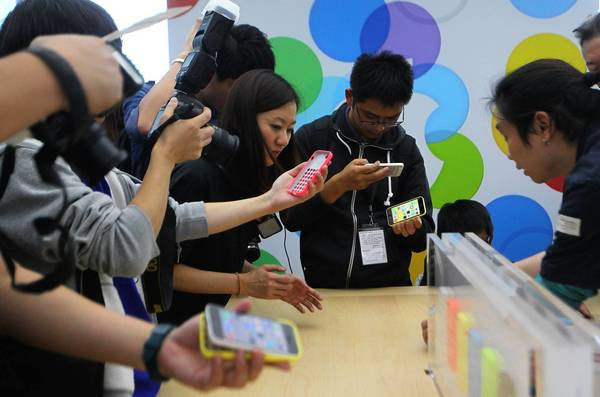 With Apple's overall growth slowing, investors and analysts believe that Apple's best opportunity to supercharge its growth is to become more competitive in newer markets. Above, journalists look at newly released Apple products during an Apple press conference in Beijing on Wednesday.