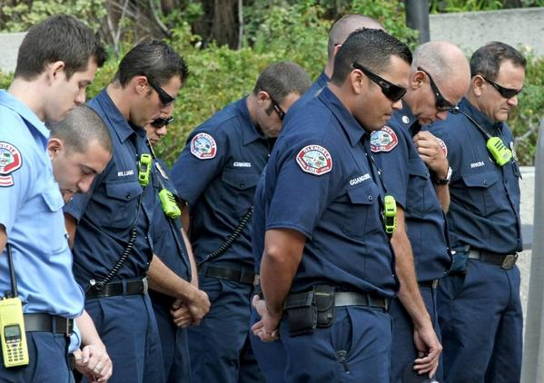 Glendale firefighters observe a moment of silence during a gathering at Perkins Plaza to honor victims on 9/11 on Wednesday, September 11, 2013.