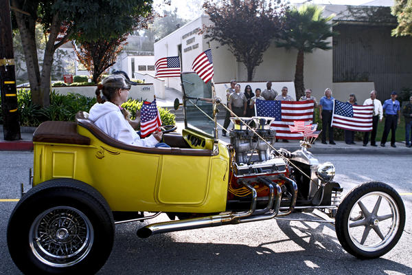 As officers waved from the sidewalk, members of the Early Rodders Car Club drove past the Los Angeles County Crescenta Valley Sheriff Station to honor heroes and victims of 9/11 in La Crescenta on Wednesday, Sept. 11, 2013. About 25 cars drove past local fire stations as well waving USA flags.
